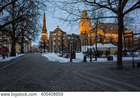Vasteras, Sweden - January 15, 2021: Buildings of Elite Stadshotellet and Vasteras Cathedral on Stora Torget square in low yellow winter sunlight, Stone paved street on foreground