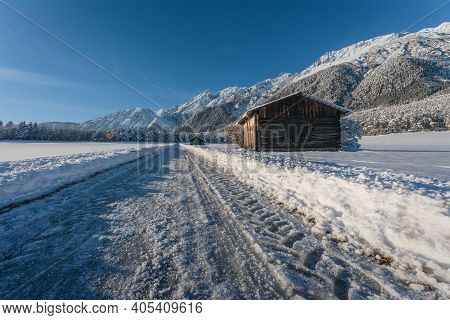 Ice Covered Walking Path Through Sunny Alpine Winter Landscape With Wooden Barn In Wildermieming, Ti