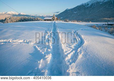 Deep Snow Trail Paths In Sunlit Alpine Winter Landscape During Sunset In Wildermieming, Tirol, Austr