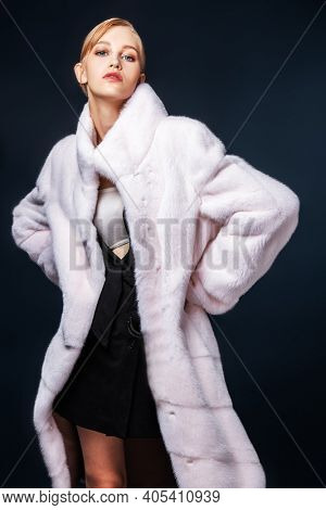Fur coat style. Fashionable model in an expensive white mink fur coat on a dark blue background with snow.