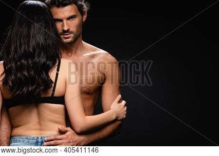 Young Shirtless Man Looking At Camera While Hugging Sexy Brunette Woman Isolated On Black.