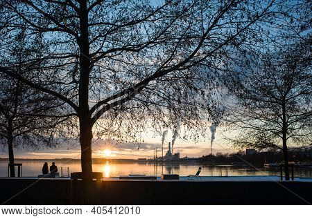 Winter sunset in Vasteras, Sweden. Couple enjoying view of low winter sun reflecting in Malaren lake, bare tree branches against twilight sky, smoke rises vertically in calm weather from plant chimney