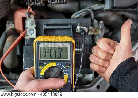 Car starter battery voltage measured with multimeter. Voltage above 14 volts as the alternator is charging the battery. Electric system working well.