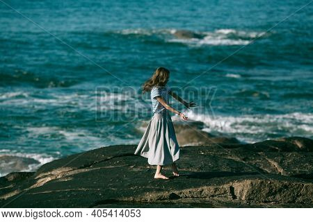The dancer woman is engaged in choreography on the rocky coast.