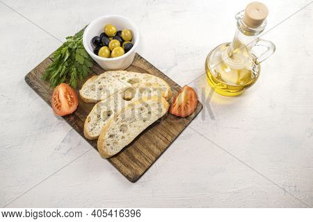 Fresh, Tasty Option For Serving Italian Focaccia. Sliced Bread On Serving Board Served With Olives,