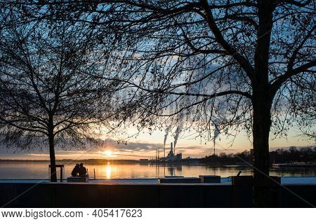 Winter sunset in Vasteras, Sweden. View of low winter sun reflecting in Malaren lake, bare tree branches against twilight sky, kissing couple, smoke rises in calm weather from recycling plant chimney