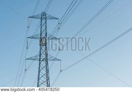 High Voltage Electric Power Lines Against A Blue Sky - With Copyspace