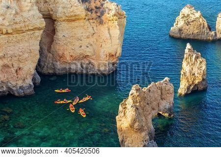 Aerial View Of Rocky Coast In Ponta Da Piedade In Lagos, With Kayak Group In Clear Ocean Water. Port
