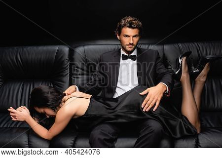 Young Man In Suit Seducing Passionate Woman While Sitting On Leather Sofa On Black.