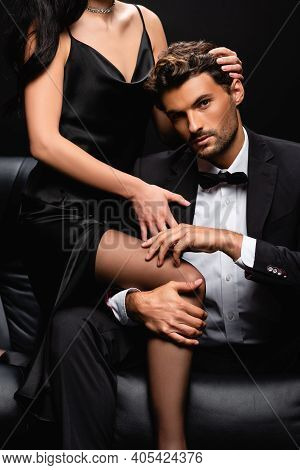 Sexy Woman In Satin Dress Seducing Elegant Man In Black Suit Isolated On Black.