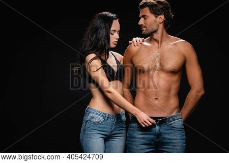 Seductive Woman In Bra Unbuttoning Jeans Of Sexy Muscular Man Isolated On Black.