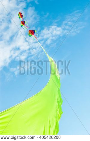 Rainbow Colored Kites Flying High On The End Of A Vibrant Green Ribbon Against A Summer Blue Sky And
