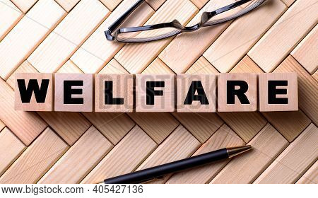 The Word Welfare Is Written On Wooden Cubes On A Wooden Background Next To A Pen And Glasses.