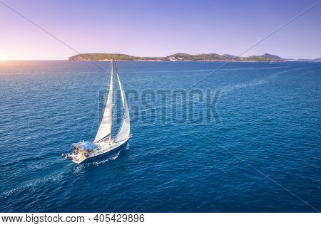 Aerial View Of Beautiful White Sailboat In Blue Sea At Bright Sunny Summer Evening. Adriatic Sea In