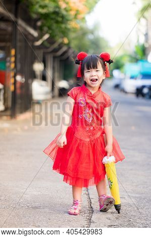 Beautiful Child Wearing Red Chinese Clothes Takes Walk On Holiday Of Traditional Chinese New Year. B