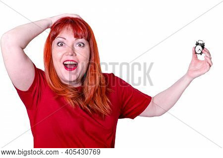 Red-haired Middle Aged Woman Wearing Red T-shirt Is Holding A Small Alarm Clock And Screaming In Sho