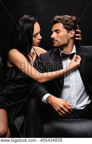 Seductive Woman In Satin Dress Seducing Young Elegant Man Isolated On Black.
