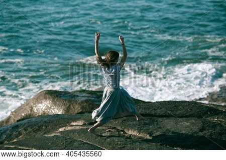 Nice dancer woman is engaged in choreography on the rocky coast of the ocean.
