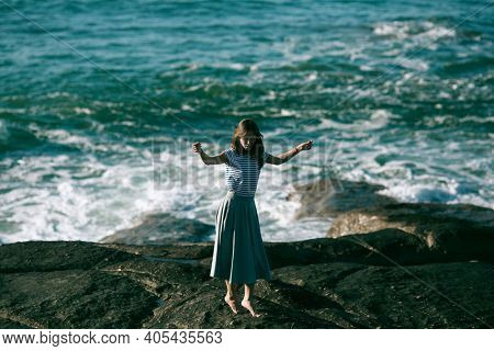 Nice young dancer woman is engaged in choreography on the rocky coast of the ocean.