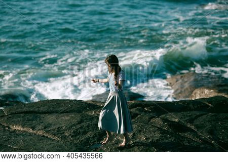 Nice young dancer woman is engaged in choreography on the rocky of the ocean.