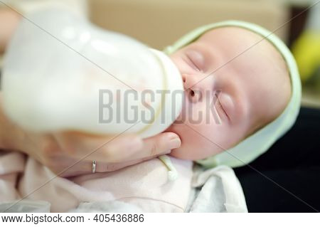 Newborn Baby Girl In Her Mother Arms. Mom Feeding Offspring Milk From Bottle. Artificial Nutrition F