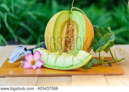 Closeup To Split The Sweet Green Melon On Wood Plate