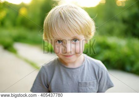 Portrait Of A Cute Green-eyed Blonde Preschooler Boy. Child Walking In Public Park On Summer Day. Be
