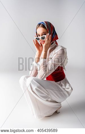 Stylish Woman In Headscarf Adjusting Sunglasses While Sitting On White.