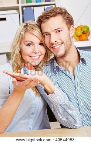Smiling happy couple holding a little house on their hands