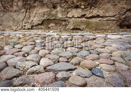 Old Granite Cobblestone Texture Background. Granite Cobblestoned Pavement And Wall. Stone Pavement T