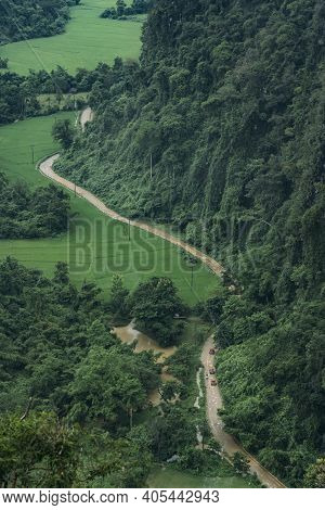 Aerial View Of Small Road Weaving Through Wet Farmland And Mountains During Monsoon Season In Vang V