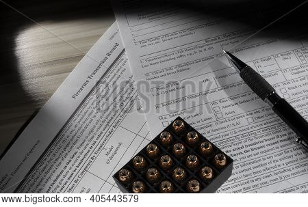 Public Domain Background Check Form For The Fbi Nics System With Ammunition And A Pen On Top.