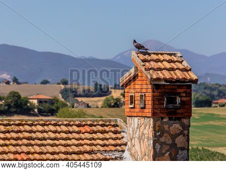 A Pigeon Perched On A Chimney Birdhouse In Corinaldo, Le Marche, Italy, With The Mountains In The Ba