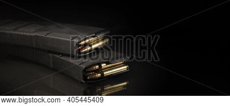A Pair Of Ar-15 Magazines Loaded With Ammunition On A Black Background With A Reflection On The Surf