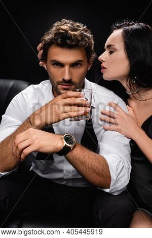 Passionate Woman Seducing Man Holding Glass Of Whiskey Isolated On Black.