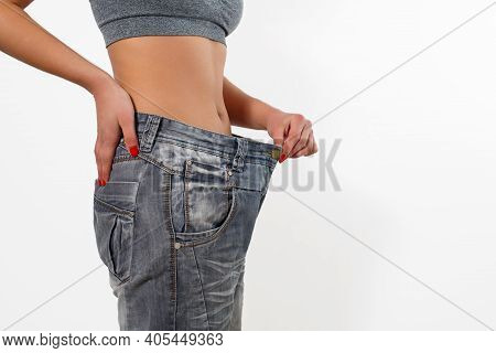 Woman After Losing Weight In Old Big Jeans. Isolated On White Background.