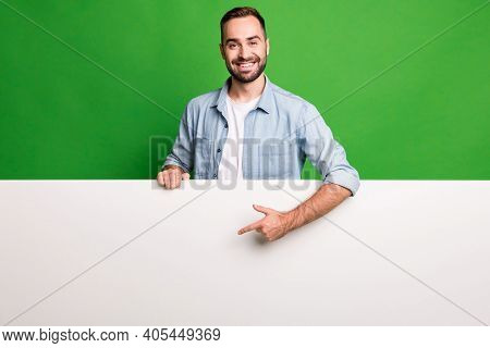 Portrait Of Optimistic Guy Point Advert Wear Blue Shirt Isolated On Vibrant Green Color Background