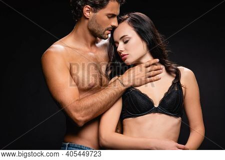Passionate Muscular Man Embracing Neck Of Sexy Brunette Woman Isolated On Black.