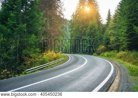 Road In Forest At Sunset In Spring. Beautiful Mountain Roadway, Trees With Green And Orange Foliage.