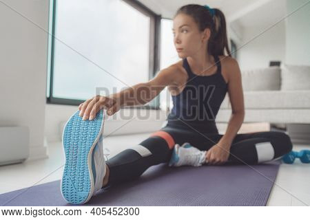 Fitness at home Asian woman stretching leg muscles on exercise mat for training pilates or hiit workout. Closeup of running shoes.