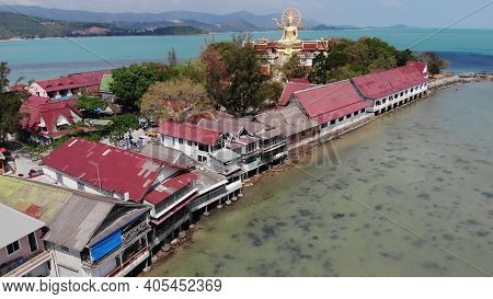 Island With Buddhist Temple And Many Houses. Aerial View Of Island With Buddhist Temple With Statue