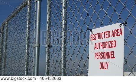 Restricted Area, Authorized Personnel Only Sign In Usa. Red Letters, Keep Off Warning On Metal Fence
