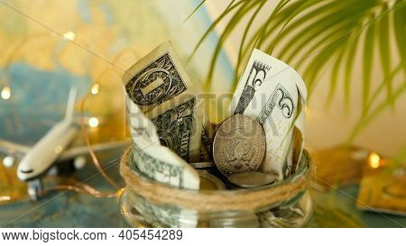 Travel Budget Concept. Money Saved For Vacation In Glass Jar On World Map Background