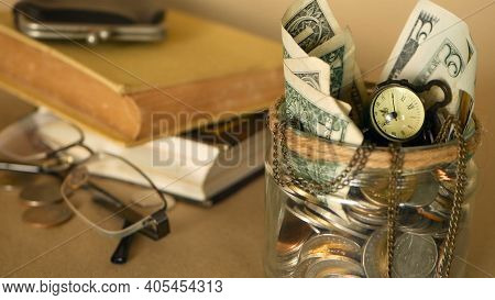 Books With Glass Penny Jar Filled With Coins And Banknotes. Tuition Or Education Financing Concept.