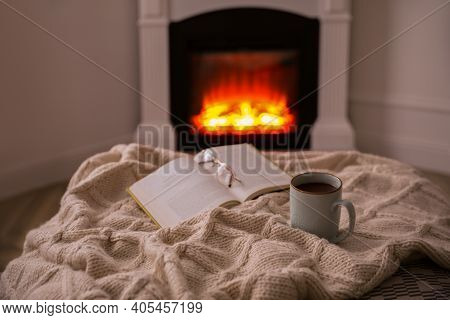 Cup Of Hot Tea And Book Near Fireplace At Home. Cozy Atmosphere