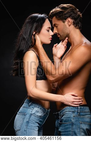 Side View Of Young Passionate Couple Embracing And Kissing Isolated On Black.