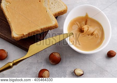 White Bowl With Natural Hazelnut Butter, Golden Knife, Hazelnuts And Toast Sandwiches On A Light Bac