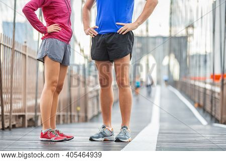 Runners legs training on Brooklyn bridge talking together before morning training run wearing run shorts and running shoes. Sports clothing concept, couple woman and man.