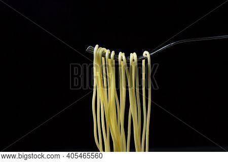 Spaghetti On A Black Background. Boiled Spaghetti On A Fork. Isolated Spaghetti. Spaghetti Hanging O