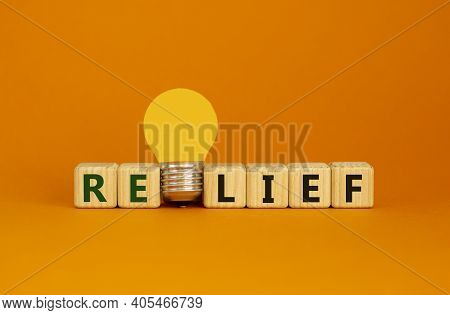 Relief Symbol. Wooden Cubes With Word 'relief'. Yellow Light Bulb. Beautiful Orange Background. Busi